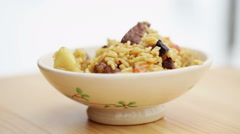 Cooking of pilaff with lamb. White plate with pilaf with mutton. Stock Footage