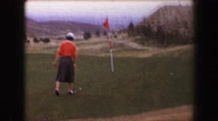 1967: Woman golfer putting on green windy day overlooking hazy valley. PALM - stock footage