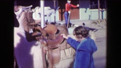 1968: Old miner giving girl llama ride around western USA tourist attraction. Stock Footage