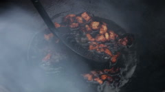Cooking soup from lamb in cauldron. Man getting cracklings from fused mutton fat - stock footage