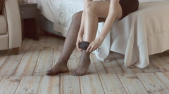 Gorgeous model in black dress puts on stockings Stock Footage