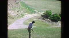 1968: Woman driving golf ball uphill on amazing natural desert landscape course. Stock Footage