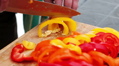 Ingredients for soup. A man cutting the bell pepper into the pieces with a knife - stock footage