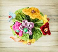 Symbolic knitted bouquet on the wooden background Stock Photos