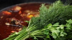 Cooking soup from lamb. A bunch of dill and parsley added in the cauldron. Stock Footage