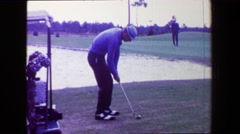 1968: Man pitching golf ball over sand trap onto green close to pin. AMES, IOWA Stock Footage