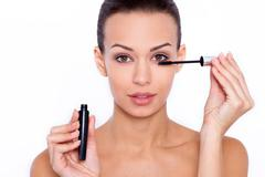 Beautiful woman applying mascara to her lashes Stock Photos