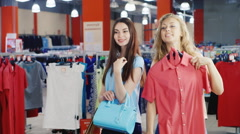 Two attractive women trying on dresses and handbags in front of a mirror in a Stock Footage