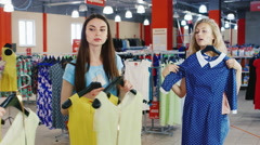 Two young women looking new summer clothes in the mirror Stock Footage