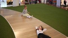 Children have fun playing drag leg little girl slide down floor mall playground Stock Footage