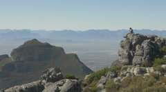4K Man Sat On Rock Looking At View From Table Mountain Top Over Cape Town City Stock Footage