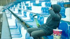 Man with beer bottle sitting at the stadium Stock Footage