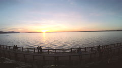 Person on a Bike Does a Wheelie at Sunset on a Waterfront Bridge Stock Footage