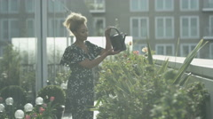 4K Portrait of smiling woman watering plants in city rooftop garden Stock Footage