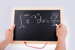 Hand writing a math problem on board Stock Photos