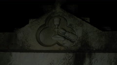 Stone cup image on crypt in cemetery at night Stock Footage