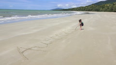 Little girl write the word Australia in the seashore sand Stock Footage