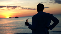 Man holding drink and admire sunset on beach  Stock Footage
