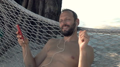 Man listening to music on cellphone on hammock, super slow motion 240fps Stock Footage