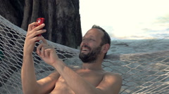 Happy man taking selfie photo with cellphone on hammock, super slow motion 240fp Stock Footage