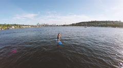 Aerial Followcam Of Young Adult Male SUP Stand Up Paddle Boarding in Lake Union Stock Footage