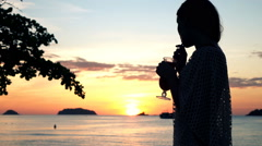 Woman drinking cocktail and admire sunset on beach Stock Footage
