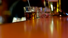 A long thin stream of whiskey from the bottle is poured into a glass. Stock Footage
