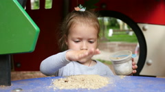 Little girl child portrait playing with sand on the playground in the park Stock Footage