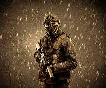 Dangerous heavily armed terrorist soldier with mask on grungy rainy backgroun Stock Photos
