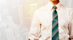 Business person with warm color overlay of city background - stock photo
