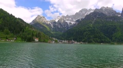 The small town of Alleghe on Lake in the Dolomites at the foot of the mountains Stock Footage