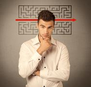 Handsome business guy solving maze - stock photo
