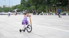 Little kid girl riding halfbike - new trendy way to cycle city slow motion.mp Stock Footage