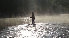Fisherman casting in early morning light on steamy river - stock footage