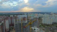Aerial. Construction site with many cranes at a big city. Sunset time - stock footage