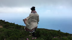 Walking Shot of Woman Wearing White Poncho on Windy Island Mountain Top Stock Footage