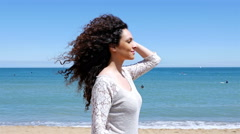 Young woman with beautiful curly hair enjoying the summer sun on the sea shore Stock Footage