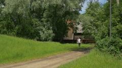 Man Sharpens the Scythe Rural Landscape Wooden Cottages in Park of Old Polish Stock Footage