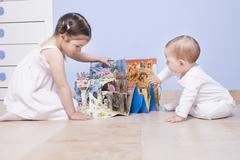 Baby boy and sister playing at toys room with pop up book - stock photo