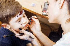 little cute child making facepaint on birthday party, zombie Apocalypse - stock photo