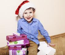 Little cute boy with Christmas gifts at home. close up emotional face on boxes Stock Photos