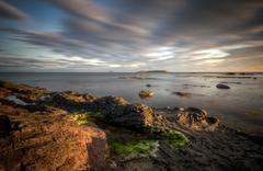 Pladda lighthouse with rocky coastline on sunset, Isle of Arran, Scotland - stock photo