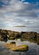 Pladda lighthouse with rocky coastline reflections, Isle of Arran, Scotland - stock photo