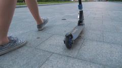 Young  woman walking with kick scooter in park, slow motion - stock footage