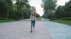 Young attractive woman stading with kick scooter in park, slow motion - stock footage