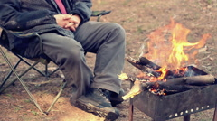 Man sitting on camp chair near bonfire. Outdoor recreation. Campfire in forest Stock Footage