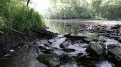tiny rocky waterfall with fisherman casting in far background - stock footage