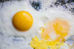 Fried eggs in a pan Stock Photos