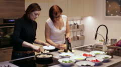 Mother and Daughter Cooking Food on a Kitchen - stock footage