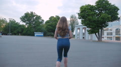 Young attractive woman riding kick scooter in park near the stadium, slow motion - stock footage